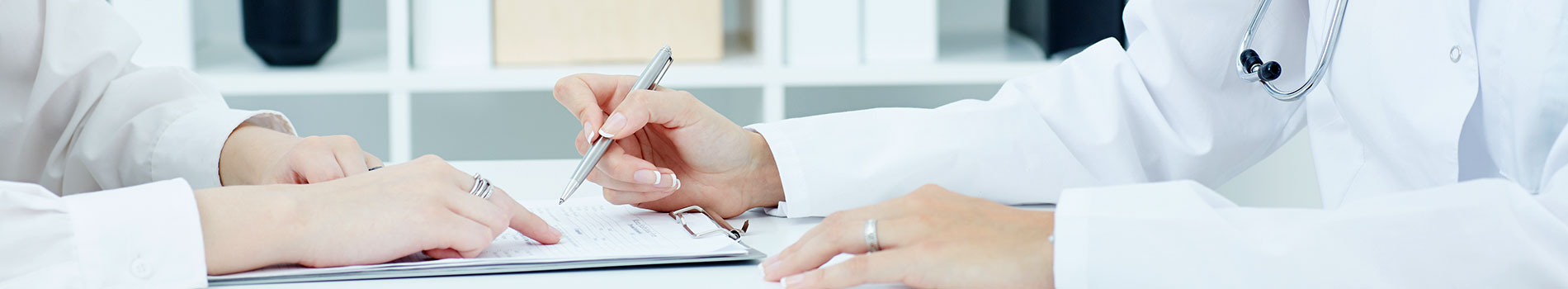 A patient, pointing to a document on a clipboard, sits with a provider